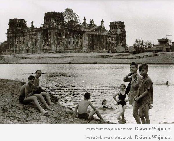 Młodzi ludzie zażywają kąpieli obok zrujnowanego Reichstagu. Berlin 1945