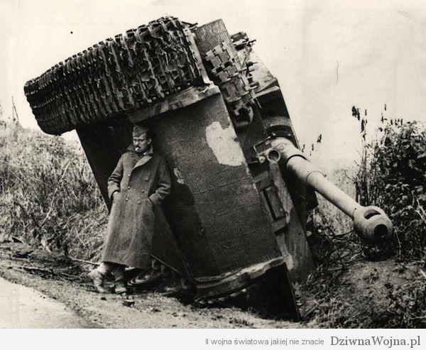 Zolnierz chowający się przed deszczem pod przewroconym na bok Tygrysem Wlochy 1944