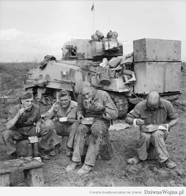 The crew of a Sherman tank fitted with deep wading equipment enjoy an evening meal beside their vehicle, 15 October 1943